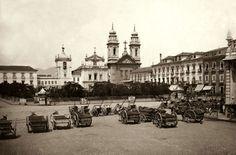 Veículos parados no Largo do Paço, atual Praça Quinze, em meados de 1890. Ao fundo, a antiga fachada da Igreja de Nossa Senhora do Carmo da Antiga Sé.
