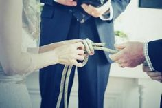 """Couple """"tying the knot"""" They tied a fisherman's knot during their ceremony. This is the strongest knot, in fact, the rope will break before the knot comes undone. The knot can be framed in a shadow box with a picture from the ceromony as a keepsake."""