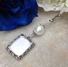 A pretty wedding bouquet photo charm in antique silver tones, featuring a white shell pearl and small Tibetan silver picture frame  NOTE: I have