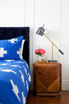 Blue bedding with white crosses, wooden night stand, gold and grey lamp, black headboard, and white walls