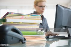 Stockfoto : Young woman working at desk in office