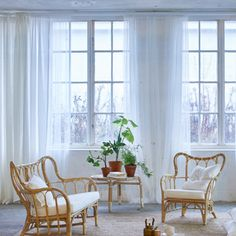 A living room featuring windows with cellular blinds with honeycomb structure that creates a layer of insulation, one layer of white sheer curtains that filters the daylight and one layer of blue curtains for privacy.