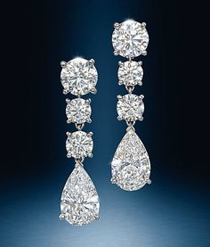 A pair of platinum and diamond drop earrings each composed of three round brilliant diamond graduating in size with a large pear shaped diamond dangling at the bottom. By Cartier