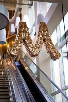 """A glittering """"M"""" for Mariano's hung over the escalator, which led guests to the second floor. Having the event on an upper level created log... Photo: Liliane Calfee"""