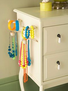 Bedroom Storage Solutions; curtain holders used to hold jewelry instead. Command hooks in the side of the dresser would probably work well also.