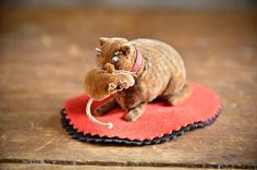 """Cat with Mouse Pen Wipe A playful striped cat, red leather collar, blue beaded eyes, holds a little velvet mouse in its mouth. 1 3/4""""high,  3 1/2"""" long."""