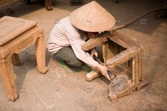 Vietnamese woman polish a chair in the craft village of Dong Ky, specialized in wood furnitures manufacture. Vietnam, Asia