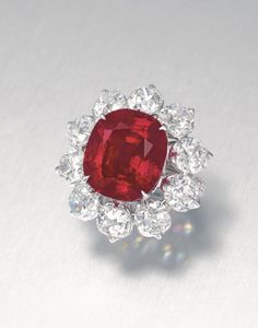 Set with a cushion-shaped ruby, weighing approximately 15.04 carats, within a cushion-shaped diamond surround, to the pavé-set circular-cut diamond three quarter-hoop, mounted in gold, ring size 5½ Accompanied by premium report no. 80282 dated 12 February 2013 from the SSEF Swiss Gemmological Institute stating that the ruby is of Burma (Myanmar) origin, with no indications of heating and the colour of this ruby may also be called 'pigeon blood red' in the trade; also accompanied by an…
