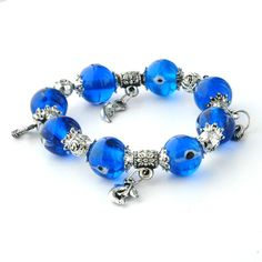 Made using eight cool blue colored glass ornaments that bear the Evil Eye symbol, this bracelet is a stunning piece of jewelry.