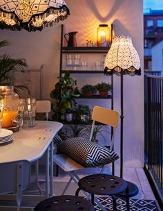 A balcony in the evening decorated with an extended table ready for dinner, a floor lamp, textiles, a shelf, plants and extra stools.