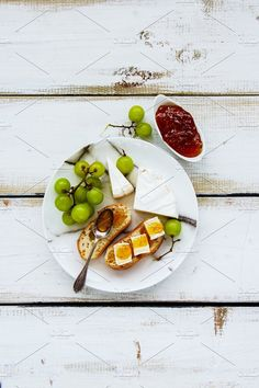 #Brie cheese and fig jam sandwiches  Tasty breakfast set on white wooden table. Brie cheese and fig jam sandwiches with fresh grapes over rustic background. Top view
