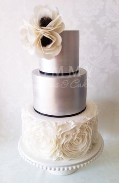 Vera Wang inspired wedding cake as featured in Real Weddings magazine Winter 2012 issue. The Rosette ruffles resembles one of Vera Wang's signature gowns topped with the sweet Black & White Anemone Flowers & Silver finish