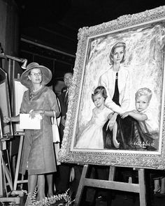 grace&family:  July 15, 1964: Princess Grace of Monaco as she looks at portrait of herself and her children, Princess Caroline, age seven and a half, and Prince Albert, age six, in Monte Carlo. Portrait was painted by Vidal Quadras, in the background behind Princess Grace.