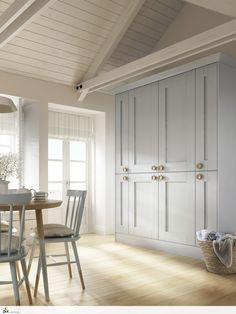 Large run of larder units create great storage in this painted pastel blue shaker kitchen. Hand painted dining table and chairs give personality, with soft painted panelled ceiling and coastal style blinds. New England inspiration photography by http://setvisionspix.co.uk/