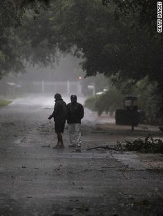 People venture out into the stormy weather as Tropical Storm Isaac begins to move ashore in Marathon, Florida, on Sunday.