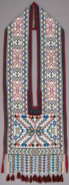 A POTAWATOMIE BEADED CLOTH BANDOLIER BAG c. 1890 composed of a single loom-woven beaded panel, stitched in numerous shades of opaque and translucent glass seed beads, with intricate geometric design, mounted on charcoal gray wool cloth, the loom-beaded panel with contiguous tab pendants, decorated with stacked triangles and zigzags, along the bottom, and terminating in red and brown wool yarn tassels