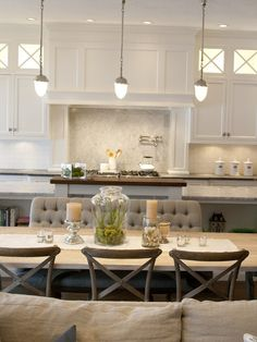 source: Alice Lane Home  Open plan kitchen dining room with Visual Comfort Lighting Garey Pendants. Gray tufted dining settee with gray, weathered wood dining table and X-back bentwood chairs. White cabinetry with soapstone counters, white subway tiled backsplash with carrara marble diamond tile over stove top.