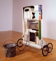 Robert Rauschenberg - 1959, Gift for Apollo. Combine: oil, pant fragments, necktie, wood, fabric, newspaper, printed reproductions on wood with metal bucket, metal chain, door knob, L brackets, metal washer, nail and rubber wheels with metal spokes (111.1 x 74.9 x 104.1 cm) The Panza Collection