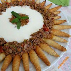 Kozalak manti. Fried plain spring rolls with yogurt and ground beef on top.