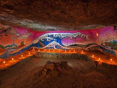 """In a sandy chamber in the catacombs of Paris, known as the """"beach,"""" a wave rolls across a wall painted (and repainted) by cataphiles in the style of Japanese printmaker Hokusai. Photographed by Stephen Alvarez for National Geographic"""