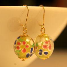 Keltaisista lamppuhelmistä tehdyt korvakorut, joissa kullanväriset, nikkelittömät koukut ja koristeosat.