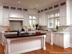 Recessed white cabinets in this kitchen add storage space without taking up much room. The white cabinets coordinate with the white countertop, sink area and black top kitchen island.