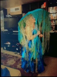 """Jellyfish umbrella costume in blue - upcycled from a formal dress. All sewn at home! Tip: Afix a """"hand zapper"""" (purchased from practical joke/magic shops) to your hand. And voila - STING!  In the dark, the battery pack string lights make this costume really stand out. Lights are strung around the perimeter of the umbrella."""