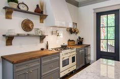 Cottage/Farmhouse kitchen, grey cabinets, butcher block counters, marble island, open shelves, black French doors...