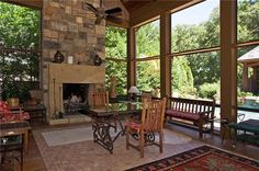 Fireplace and high walls in this screened porch equal comfortable luxury space