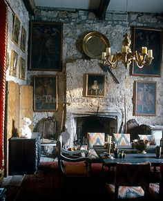 Old portrait paintings hang on the rough surface of the stone wall in the dining room at Chillingham Castle