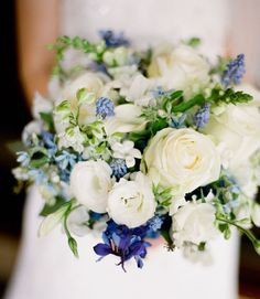 Delicate delphinium, lisianthus, roses, larkspur, snapdragons, and fragrant grape muscari and stephanotis blossoms gathered in a wonderfully crisp blue and white bridal bouquet.  Image by HA! Photography