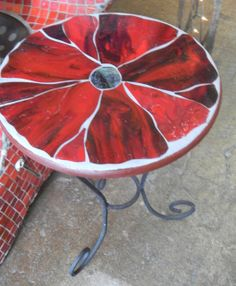 Beautiful red floral stained glass mosaic tabletop on wrought iron base.