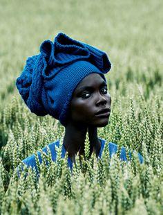 Fotografia de formas e cores de uma mulher negra em uma plantação. Riqueza de detalhes.