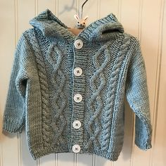 Perfect for keeping warm on chilly days, this classic hooded cardigan is suitable for both boys and girls and is available in sizes from 3 months to 4 years. It is knit seamlessly from the bottom up and features a simple drop shoulder construction and a fun to work cable design on the fronts, back and sleeves. Both charted and written instructions are included for the cable pattern.