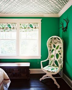 Decor - A botanical-print chair in a bedroom with green walls and a wallpapered ceiling