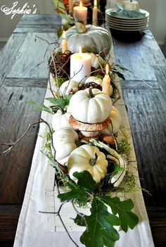 Fall Decorating. Rustic table with a white painted wood box - crate, holding pumpkins,candles, vines, leaves, a rusty urn...