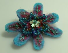 felt pin with beads and embroidery.