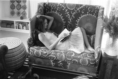 Woman reading a book on a couch.