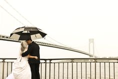 This couple braved the rain for a shot in front of which NYC bridge? We bet you can guess! #NYC