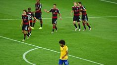 A dejected Dante of Brazil reacts as Andre Schuerrle of Germany celebrates scoring