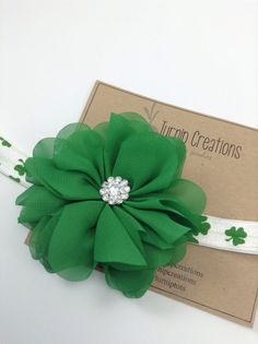A classic St Pattys Day headband! A green ballerina flower with a rhinestone on a shamrock print headband. PLEASE INDICATE SIZE AT CHECKOUT. If