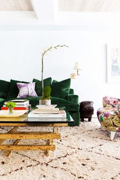 Green velvet sofa with purple pillow, coffee table with books, and floral chair