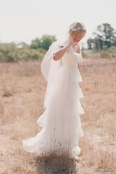 tiered empire wedding dress with cap sleeves by Myra Callan.