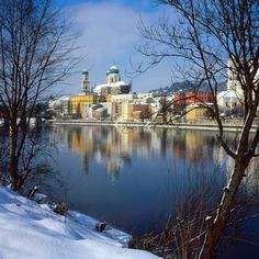Snowy churches in Passau, a town in Bavaria, Germany. The river in the foreground is the Danube.