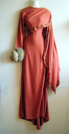 late 1940s evening gown in a muted salmon pink crepe with beaded trim and giant fox fur cuffs