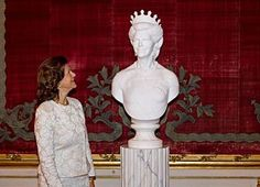 Queen Silvia of Sweden looking at  a marble bust of herself wearing the Nine Prong tiara