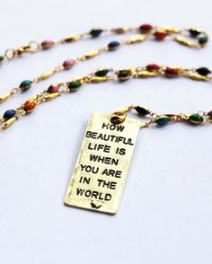 """See Beautiful """"How Beautiful"""" necklace. Skillfully handcrafted in India, this necklace is stamped with words of wisdom and serves as a reminder that you offer so much beautiful to the world, simply by being in it. Your purchase gives back! Choose a See Beautiful Giving Initiative at check out and a portion of your purchase will support a cause dear to our hearts. Click through to learn more. Specs: Gold plated & Iron. Handmade in India. Approximately 37 inches."""