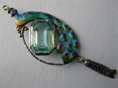 An Art Nouveau silver and enamel peacock pendant.