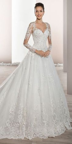 Delicately beaded appliques embellish this romantic Tulle Ball gown with Sweetheart neckline and elegant sheer sleeves with lace accents that flow into a dramatic, low sheer back with button closure. The back features a stunning lace embellished Cathedral train.