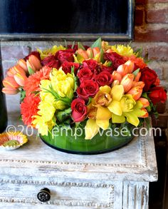 Red Roses, Yellow and Orange Tulips, Yellow Cymbidium Orchids and Orange Dahlias in a low Cylinder Glass Vase lined with Tea Leaves